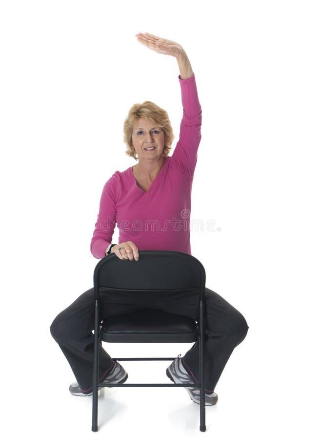 hög sträckande kvinna för stol arkivbild