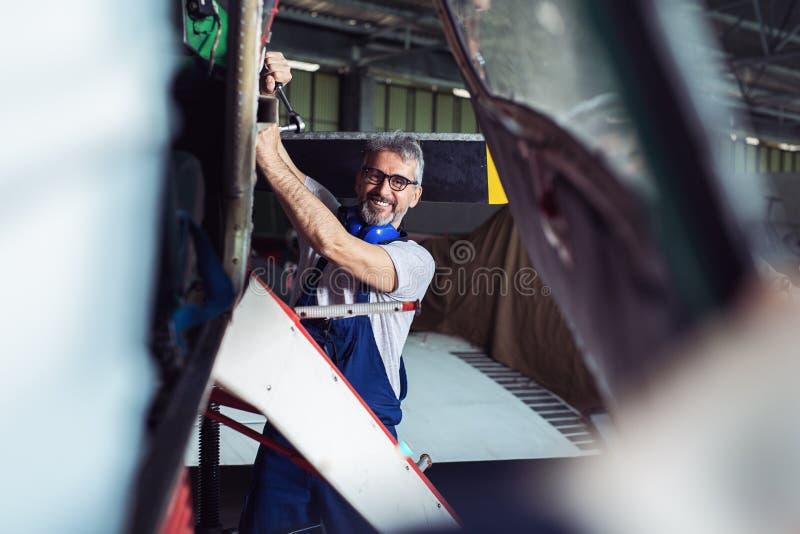 Hög tekniker som reparerar flygplanmotorn arkivfoton