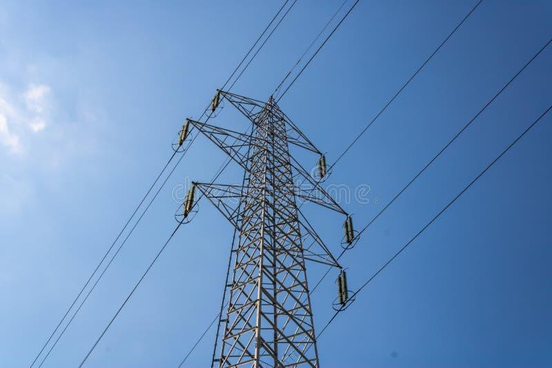 Hög tråd för spänningspolkabel på en solig dag med blå himmel, elektricitetsraster - bild royaltyfri foto