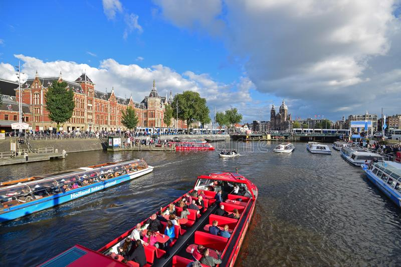 Hög trafik av att passera fartygkanalkryssningar som fylls med massturister på flodkanalen med den Amsterdam centralstationen royaltyfria bilder