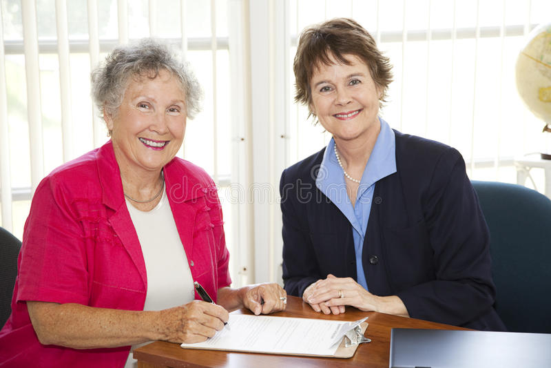hög undertecknande kvinna för skrivbordsarbete royaltyfri bild