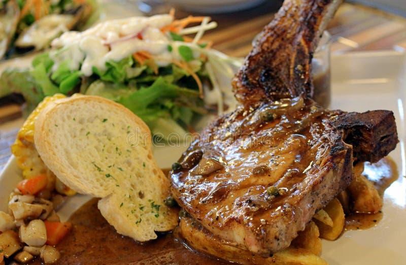 Hög upplösning grillade stöd för griskött för ` för `-kurobuta, och svartpepparsås tjänade som med potatiskilar, bröd och sallad royaltyfri fotografi