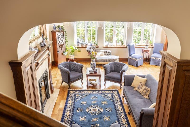 Hög vinkel av en rustical vardagsruminre med en blå filt, fåtöljer, en soffa och ett trägolv royaltyfri bild