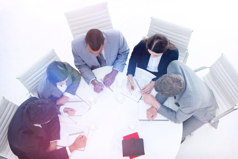 Hög vinkel av ett olikt sammanträde för affärsgrupp runt om en konferenstabell royaltyfri bild