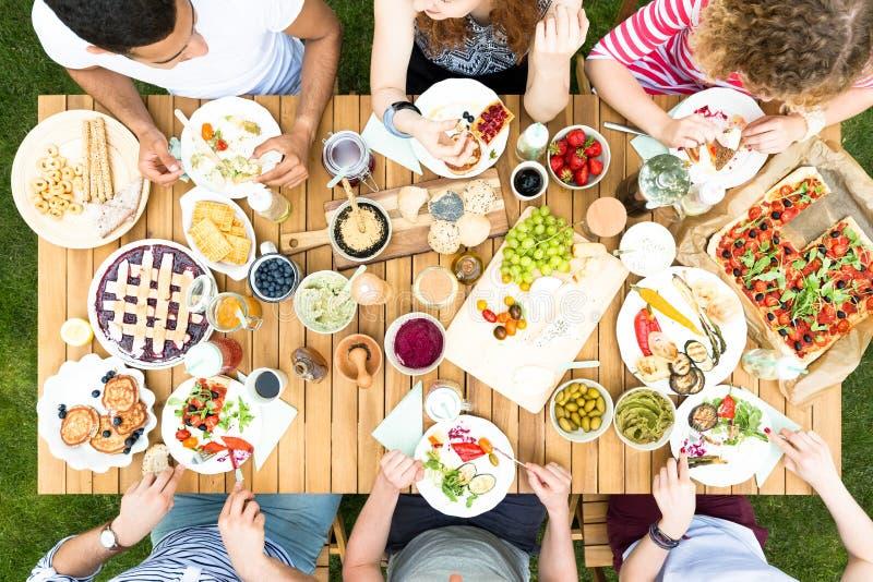 Hög vinkel av vänner som äter pizza och frukt under en celebratio royaltyfri foto
