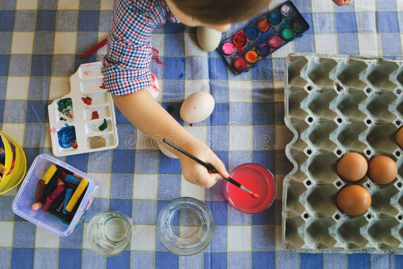 Hög vinkel på Little Boy genom att använda vattenfärger för att måla påskägg hemma arkivfoto