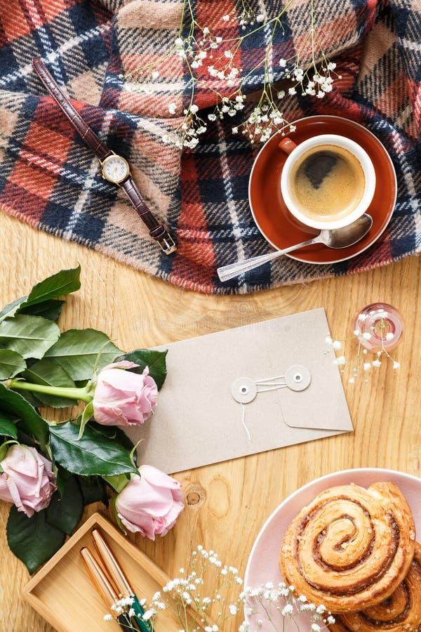 Hög vinkel på rosa rosor på träskrivbordet med koppen kaffe och b arkivbild