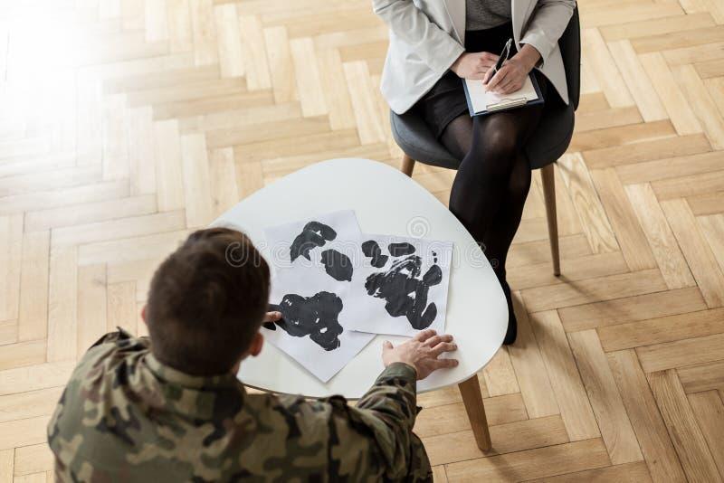 Hög vinkel på soldaten som väljer bilden under möte med psykiatern arkivbilder