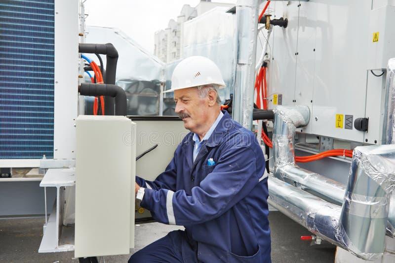 Hög vuxen elektrikerteknikerarbetare royaltyfri bild