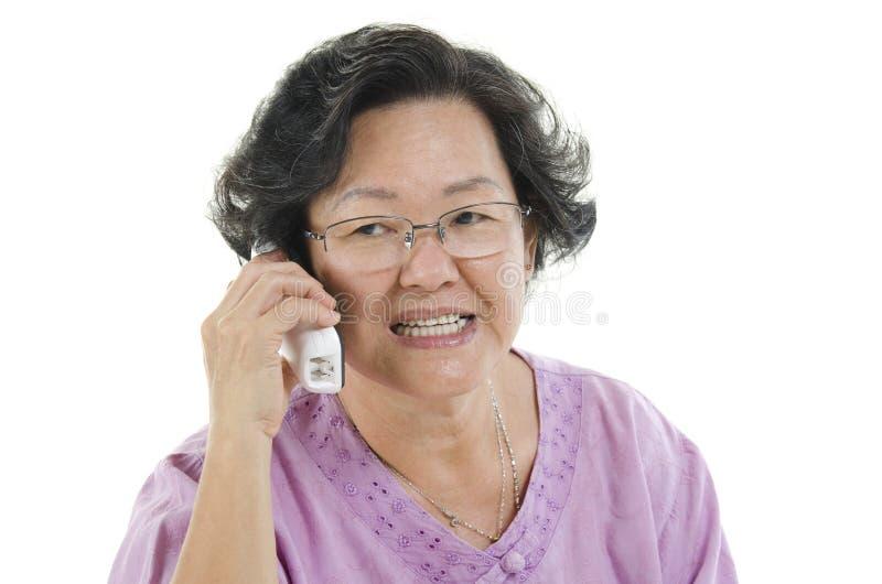 Hög vuxen kvinna på telefonen royaltyfria foton