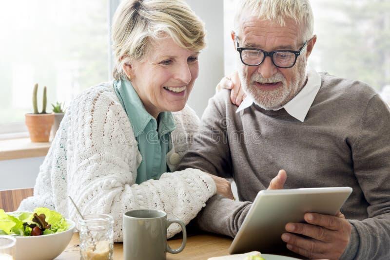 Hög vuxen människa som använder begrepp för Digital apparatminnestavla royaltyfria bilder