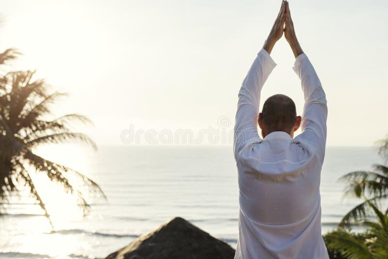 Hög vuxen praktiserande yoga nära stranden arkivbilder