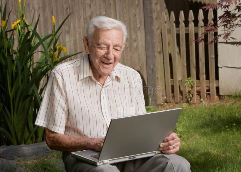 Hög working för gamal man på datoren royaltyfria foton