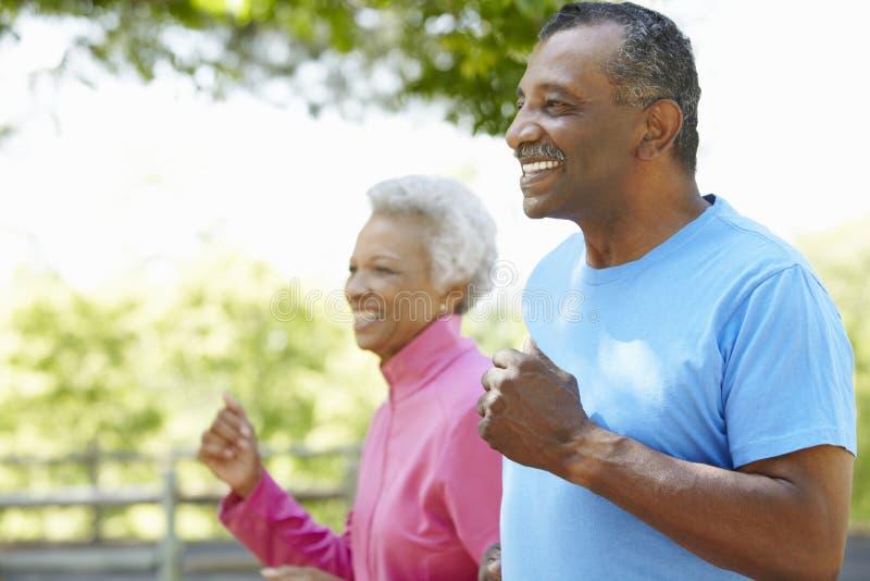 Höga afrikansk amerikanpar som in joggar, parkerar royaltyfri fotografi