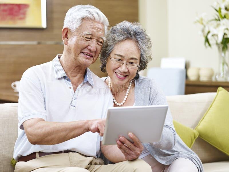 Höga asiatiska par genom att använda en minnestavladator tillsammans royaltyfri foto