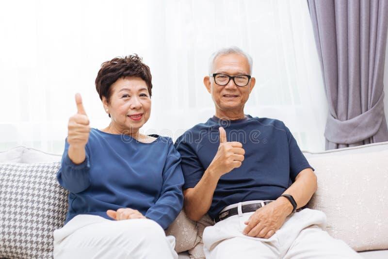 Höga asiatiska par som ser kameran och ger upp tummar, medan sitta på soffan hemma royaltyfria bilder