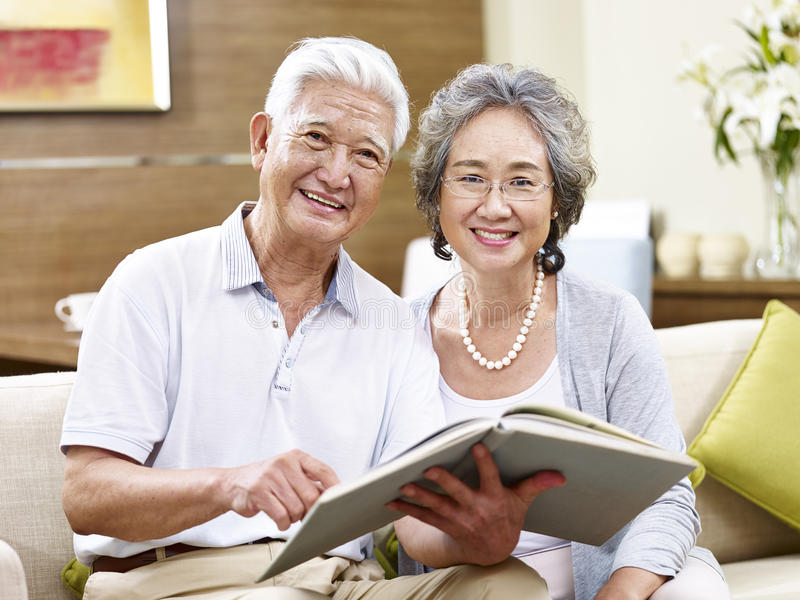 Höga asiatiska par som tillsammans läser en bok royaltyfri bild