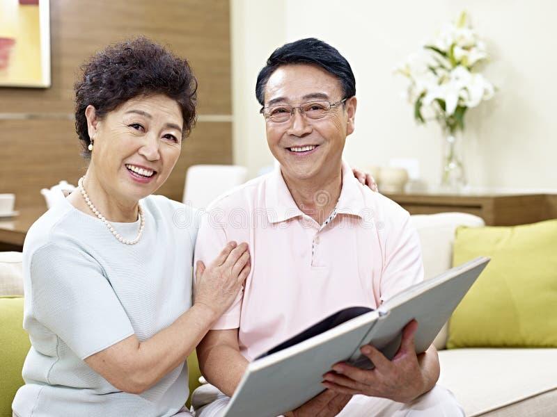 Höga asiatiska par som tillsammans läser en bok royaltyfri foto