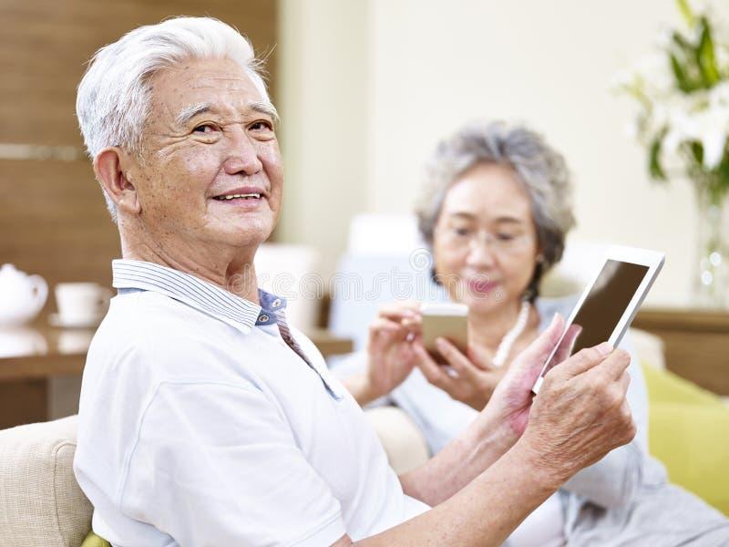 Höga asiatiska par som tycker om modern teknologi royaltyfria bilder