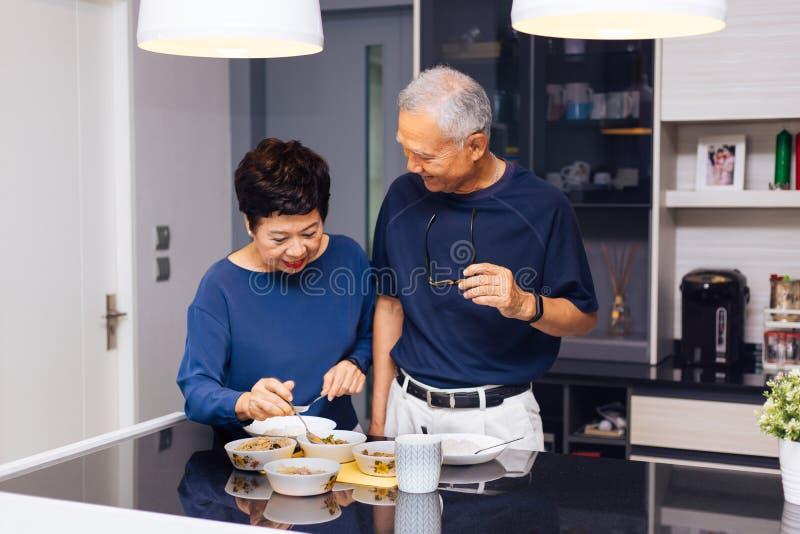 Höga asiatiska parmorföräldrar som tillsammans lagar mat, medan kvinnan matar mat till mannen på köket Slitstarkt förhållande arkivfoton