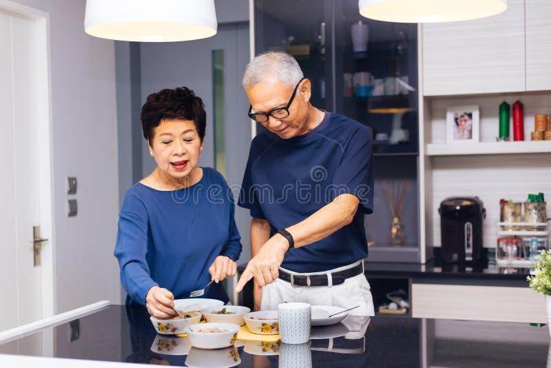 Höga asiatiska parmorföräldrar som tillsammans lagar mat, medan kvinnan matar mat till mannen på köket Slitstarkt förhållande arkivfoto