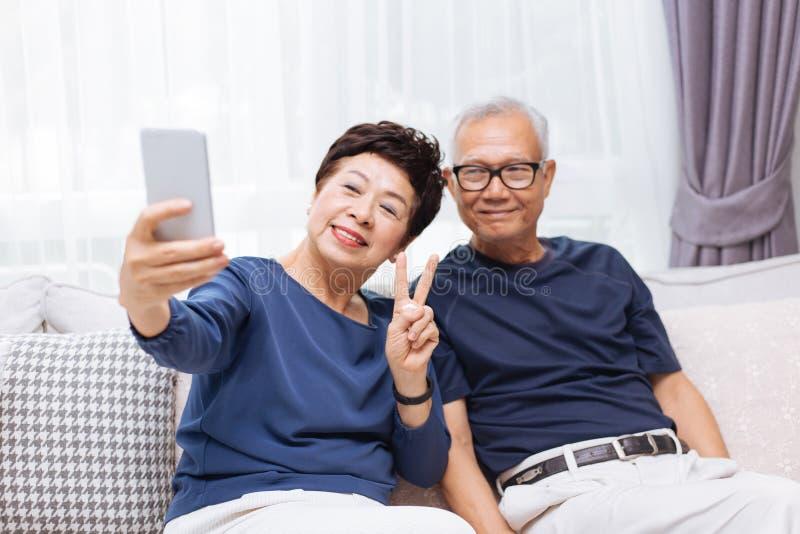 Höga asiatiska parmorföräldrar som tillsammans tar ett selfiefoto hemma royaltyfria bilder