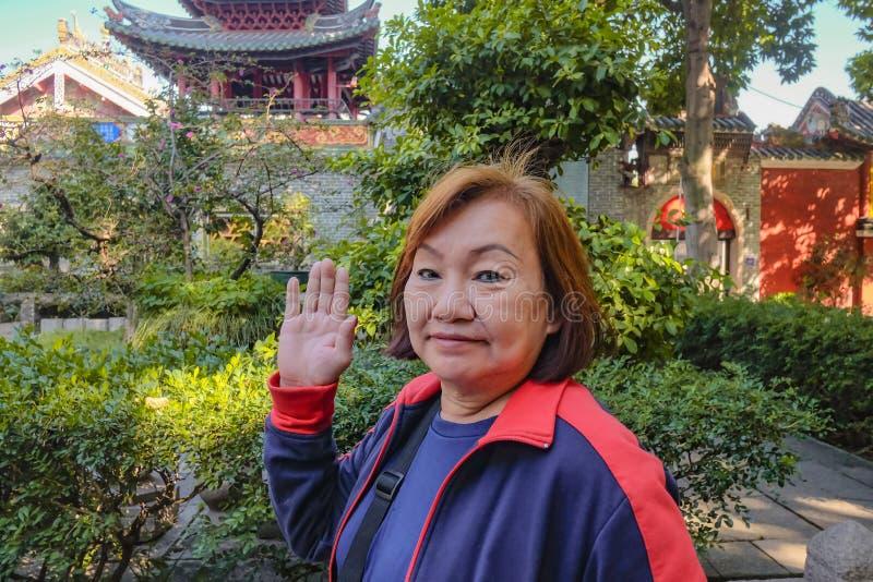 Höga asiatiska turist- kvinnor som går stund, säger 'hi 'till kameran i den släkt- templet arkivbilder