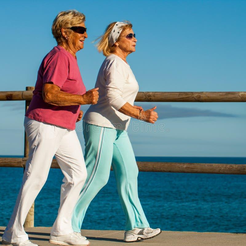 Höga damer som joggar på sjösidan. arkivfoton