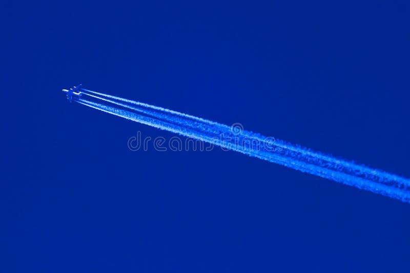 Höga flygstråle och contrails royaltyfria foton