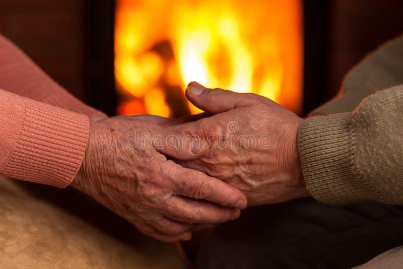 Höga gamla händer som framme tröstar sig av spisen royaltyfri bild