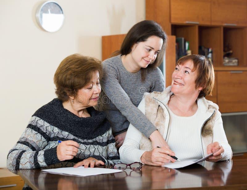 Höga gulliga le kvinnor som gör skallr på notarius publicukontoret arkivbild