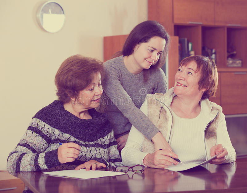 Höga gulliga le kvinnor som gör skallr på notarius publicukontoret royaltyfri fotografi