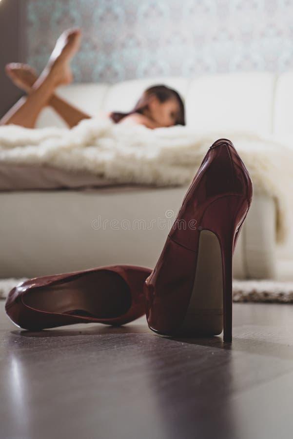 Höga häl framme av det defocused kvinnliga sovrummet Sexig erotisk kvinna som kopplar av på säng Den attraktiva kvinnlign kopplar arkivbild