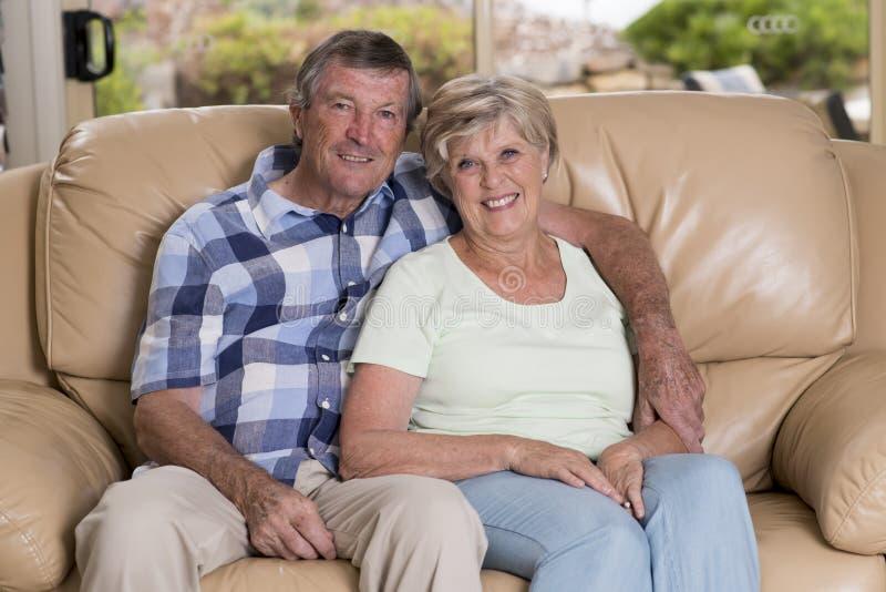 Höga härliga mellersta ålderpar omkring 70 år gammal le lycklig tillsammans hemmastadd vardagsrumsoffasoffa som ser söt i liv fotografering för bildbyråer