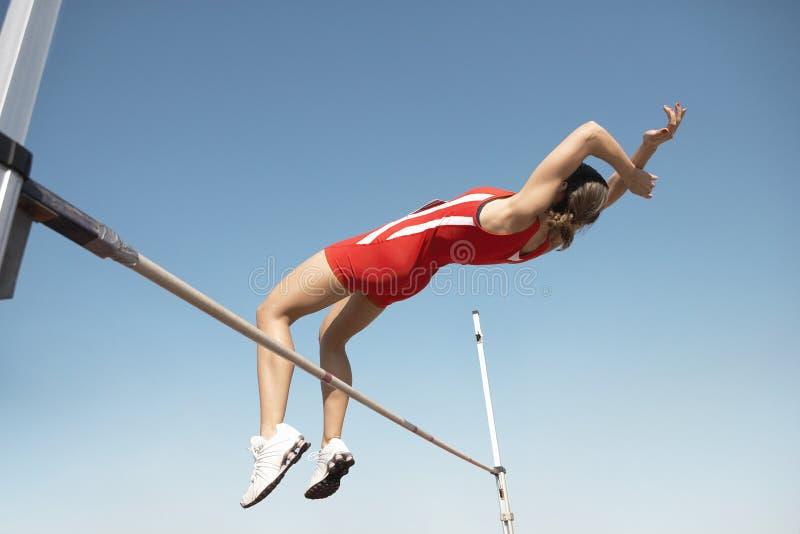 Höga Jumper In Midair Over Bar arkivfoton