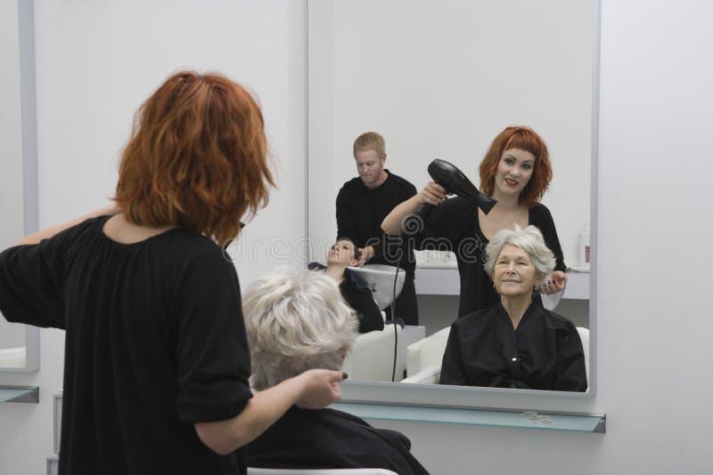 Höga kvinnas för stylistslaguttorkning hår i salong royaltyfri foto