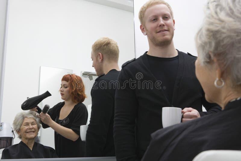 Höga kvinnas för stylistslaguttorkning hår i salong arkivbild