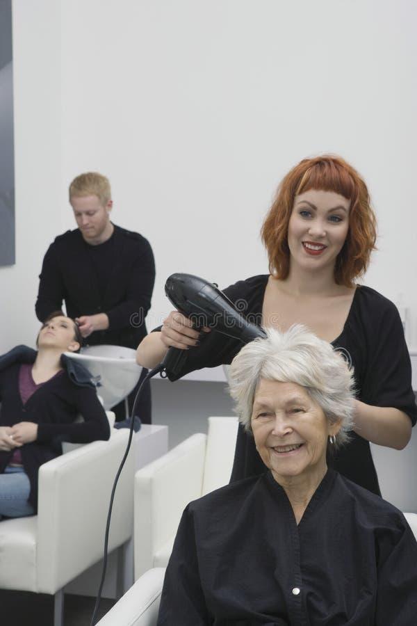 Höga kvinnas för stylistslaguttorkning hår i salong royaltyfri bild