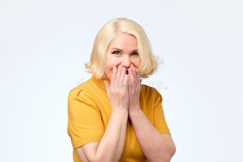 Höga kvinnliga fniss joyfully, täcker munnen, som försök stoppar att skratta fotografering för bildbyråer