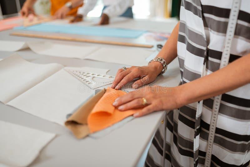 Höga kvinnliga händer för modeformgivare som rymmer tygprövkopior royaltyfria bilder