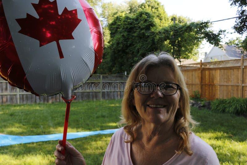 Höga kvinnor åldrades 60 till 65 som rymmer en Kanada dagballong för att vara patriotiska royaltyfri bild