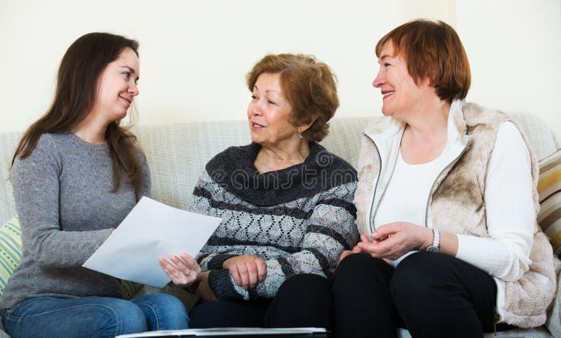 Höga kvinnor som konsulterar med bankrörelsemedlet arkivbild
