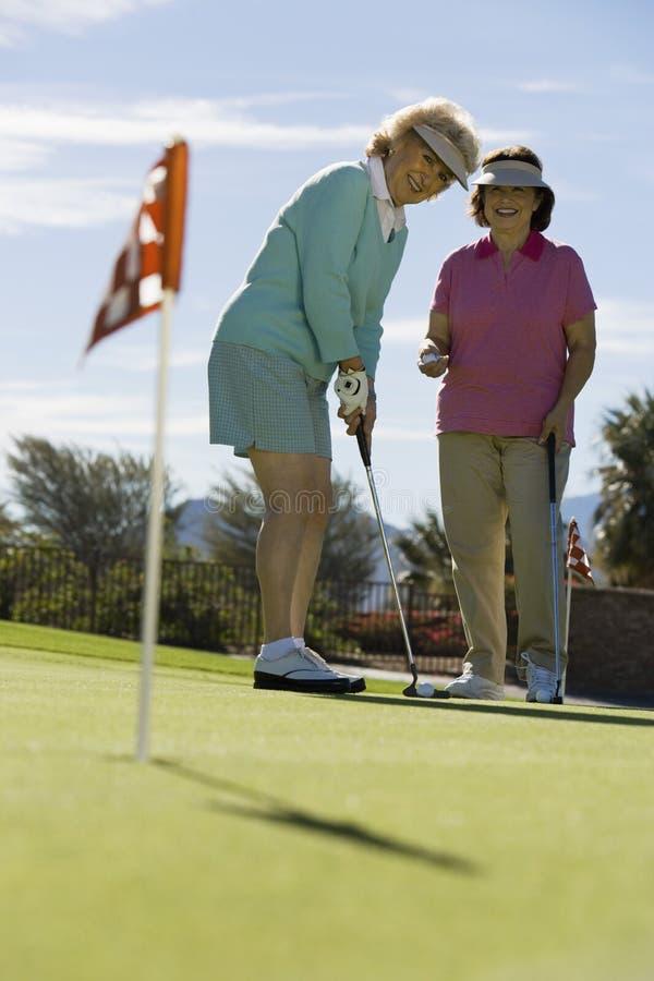 Höga kvinnor som leker Golf arkivbild
