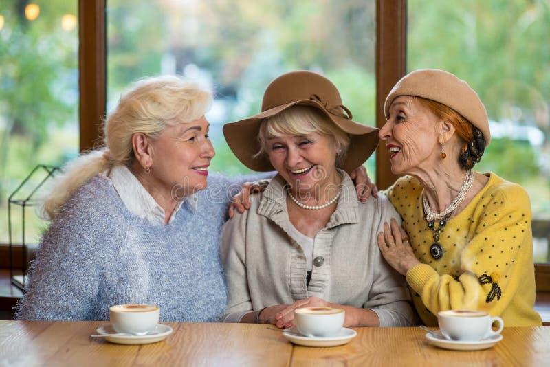 Höga kvinnor som skrattar på tabellen arkivbilder