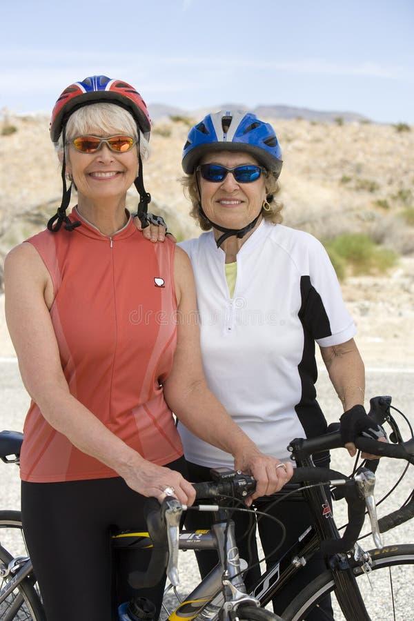 Höga kvinnor som står med cykeln arkivbild