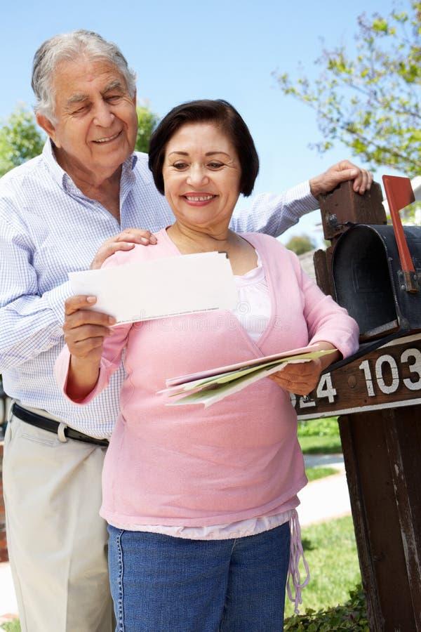 Höga latinamerikanska par som kontrollerar brevlådan royaltyfri foto