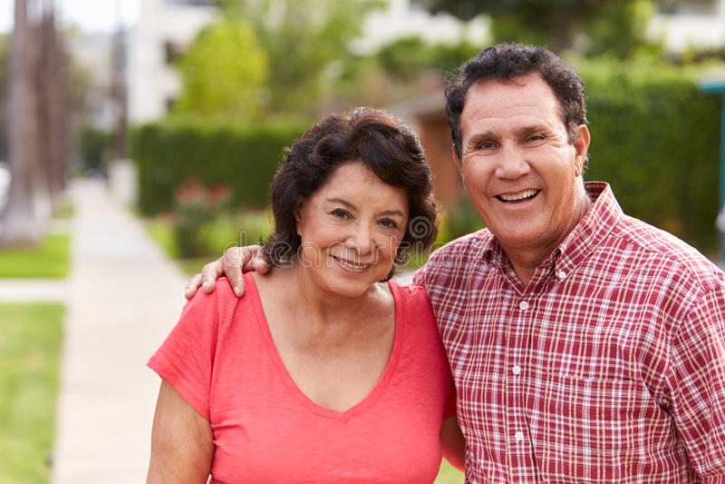 Höga latinamerikanska par som tillsammans promenerar trottoaren royaltyfri fotografi