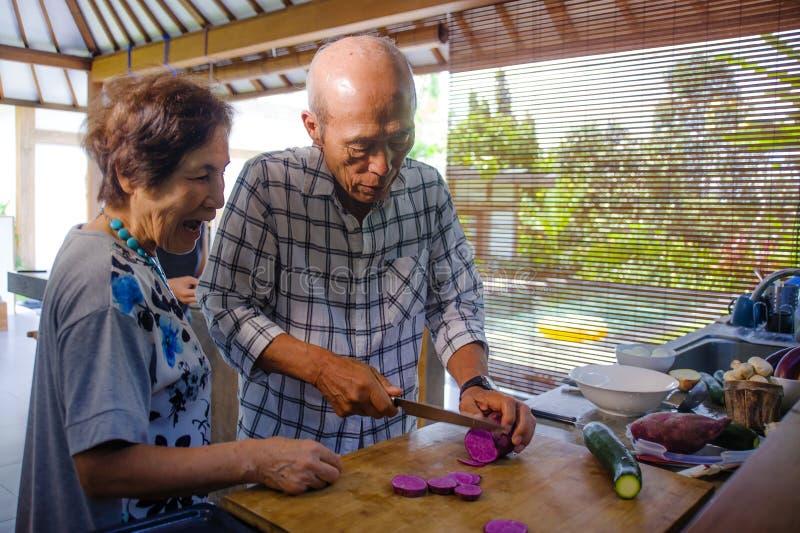 Höga lyckliga och härliga pensionerade asiatiska japanska par som tillsammans lagar mat hemmastatt kök som tycker om förbereda må royaltyfria bilder
