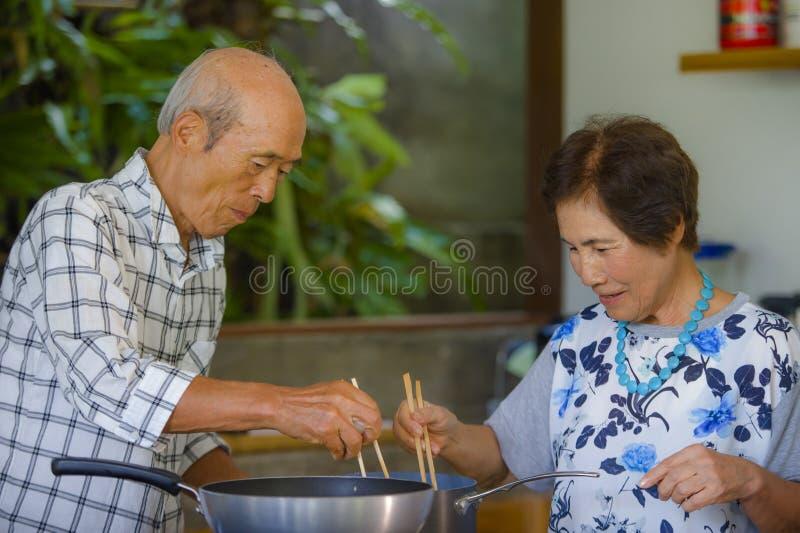 Höga lyckliga och härliga pensionerade asiatiska japanska par som tillsammans lagar mat hemmastatt kök som tycker om förbereda må fotografering för bildbyråer