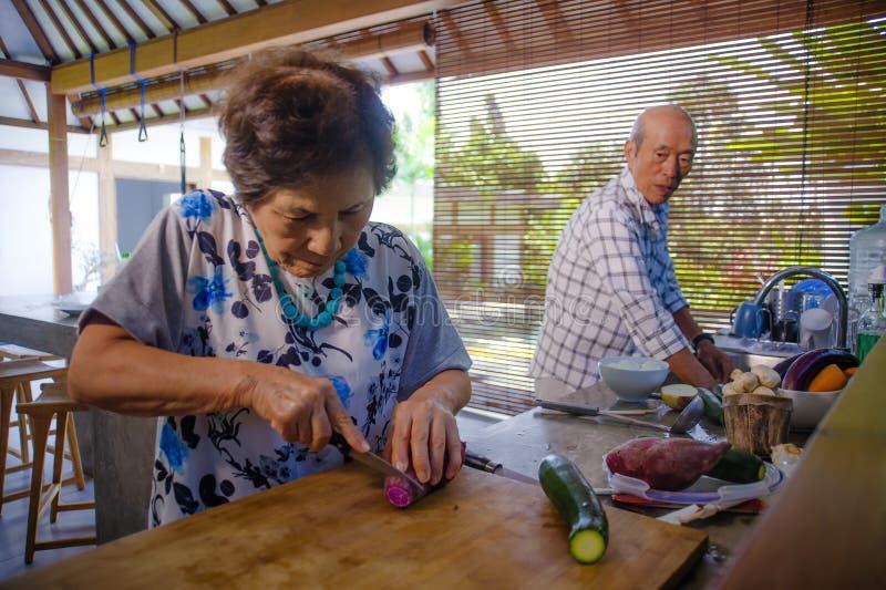 Höga lyckliga och härliga pensionerade asiatiska japanska par som tillsammans lagar mat hemmastatt kök som tycker om förbereda må arkivbilder